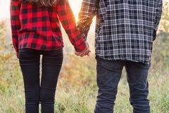 Zamyka w górę młodego człowieka i jego dziewczyna w przypadkowych ubraniach trzyma ręki do siebie Szczęśliwa para z gitarą ma zdjęcie royalty free