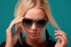 Zamyka W górę Modnej blondynki w Retro Stylowych okularach przeciwsłonecznych na Turkusowym tle zdjęcie royalty free