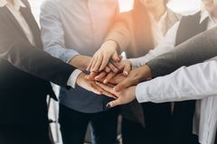 Zamyka w górę odgórnego widoku młodzi ludzie biznesu stawia ich ręki wpólnie Sterta ręki Jedność i pracy zespołowej pojęcie zdjęcia stock