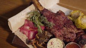 Zamyka w górę piec na grillu mięsa z ziobro kości lying on the beach na pita z czerwoną kapustą, kukurudza, pieczarki, marchewka  zbiory wideo
