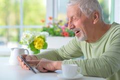 Zamyka w górę portreta starszy mężczyzna używa pastylkę podczas gdy pijący herbaty obrazy stock