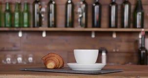 Zamyka w górę strzału croissant na ten sam tacy z filiżanka kawy zbiory