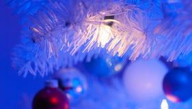 Zamyka w górę światła białego sznurek światła na białych bożych narodzeniach drzewnych z ornamentami w tle zdjęcie royalty free