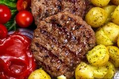 Zamyka w górę Świeżych soczystych grillów hamburgerów, słuzyć z ketchupem, młodymi grulami, pomidorami i warzywami, głębii pola p Obraz Stock