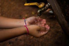 Zamyka w górę Azjatyckiej chłopiec metalu wodnego faucet otwartej pustej ziemi Obraz Royalty Free