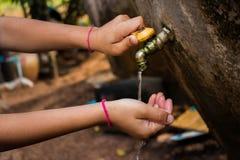 Zamyka w górę Azjatyckiej chłopiec metalu wodnego faucet otwartej pustej ziemi Obraz Stock