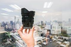 Zamyka w górę chwyt kamery obiektywu w ręce Zdjęcie Stock