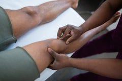 Zamyka w górę ciemnoskórego masażu terapeuty masowania kolana zdjęcia royalty free
