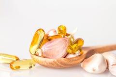 Zamyka w górę czosnku i oliwi kapsuły gel nadprogram w drewnianej łyżce Fotografia Royalty Free