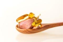 Zamyka w górę czosnku i oliwi kapsuły gel nadprogram w drewnianej łyżce Zdjęcie Royalty Free
