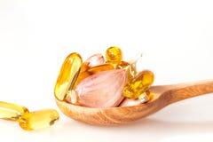 Zamyka w górę czosnku i oliwi kapsuły gel nadprogram w drewnianej łyżce Fotografia Stock