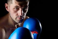 Zamyka w górę depresja klucza portreta agresywny mięśniowy wojownik, pokazuje jego pięść odizolowywającą na ciemnym tle Zdjęcia Stock