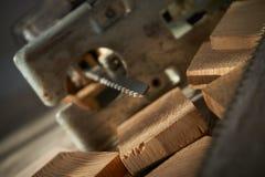 Zamyka w górę elektrycznego wyrzynarki ostrza i drewnianych cegieł obrazy stock