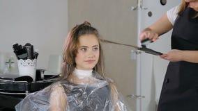 Zamyka w górę fachowego fryzjera, stylista barwi nastoletniego dziewczyna włosy zbiory wideo