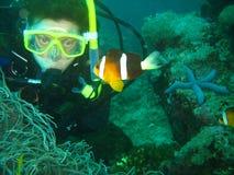Zamyka w górę fotografii błazen ryba Młoda kobieta akwalungu nurek jest przyglądający błazen ryba obraz royalty free