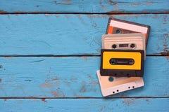 Zamyka w górę fotografii rocznik kasety taśma nad aqua drewnianym stołem Odgórny widok Retro filtrujący obraz stock