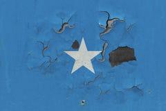 Zamyka w górę grungy, uszkadzającej i wietrzejącej Somalia flagi na ścianie struga daleko farbę widzieć wśrodku powierzchni, zdjęcie stock
