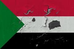 Zamyka w górę grungy, uszkadzającej i wietrzejącej Sudan flagi na ścianie struga daleko farbę widzieć wśrodku powierzchni, zdjęcia stock