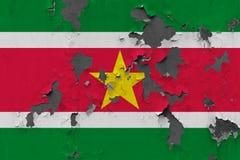 Zamyka w górę grungy, uszkadzającej i wietrzejącej Suriname flagi na ścianie struga daleko farbę widzieć wśrodku powierzchni, obrazy stock
