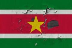 Zamyka w górę grungy, uszkadzającej i wietrzejącej Suriname flagi na ścianie struga daleko farbę widzieć wśrodku powierzchni, zdjęcia royalty free