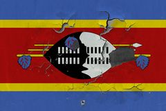 Zamyka w górę grungy, uszkadzającej i wietrzejącej Swaziland flagi na ścianie struga daleko farbę widzieć wśrodku powierzchni, obrazy stock