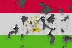 Zamyka w górę grungy, uszkadzającej i wietrzejącej Tajikistan flagi na ścianie struga daleko farbę widzieć wśrodku powierzchni, obraz royalty free