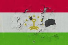Zamyka w górę grungy, uszkadzającej i wietrzejącej Tajikistan flagi na ścianie struga daleko farbę widzieć wśrodku powierzchni, zdjęcia stock