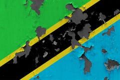 Zamyka w górę grungy, uszkadzającej i wietrzejącej Tanzania flagi na ścianie struga daleko farbę widzieć wśrodku powierzchni, zdjęcia stock