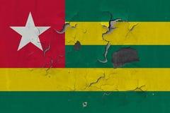 Zamyka w górę grungy, uszkadzającej i wietrzejącej Togo flagi na ścianie struga daleko farbę widzieć wśrodku powierzchni, zdjęcie royalty free