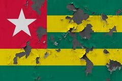 Zamyka w górę grungy, uszkadzającej i wietrzejącej Togo flagi na ścianie struga daleko farbę widzieć wśrodku powierzchni, obraz stock