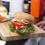 Zamyka w górę hamburgeru na drewniany szerokim fotografia stock