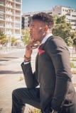 Zamyka w górę jeden potomstw i atrakcyjnego czarnego biznesmena patrzeje kamerę przed nowożytnym budynkiem w mieście jest ubranym zdjęcia royalty free