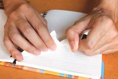 Zamyka w górę kobiety ręki rozdziera lub drzeje białego papier na notatniku fotografia royalty free