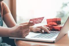 Zamyka w górę kobiety ręki trzyma kredytową kartę i pisać na maszynie laptopu keyboa Zdjęcia Royalty Free