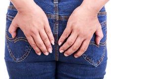 Zamyka w górę kobiety ręki trzyma zadek: Pojęcie hemoroidy obrazy stock