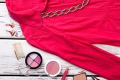 Zamyka w górę kosmetycznych kobiety ` s akcesoriów i czerwieni ubrań Fotografia Stock
