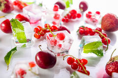 Zamyka w górę kostek lodu z świeżymi jagodami wśród zamarzniętej wiśni i wybija monety liście na białym tle, truskawka selekcyjna Zdjęcie Stock