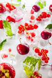 Zamyka w górę kostek lodu z świeżymi jagodami wśród zamarzniętej wiśni i wybija monety liście na białym tle, truskawka Selekcyjna Obraz Stock