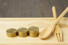 Zamyka w górę kroka złociste monety i łyżka z rozwidleniem Zdjęcia Stock