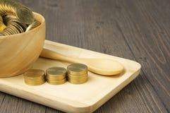 Zamyka w górę kroka złociste monety z monetami w filiżance Zdjęcia Stock