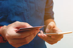 Zamyka w górę mężczyzna używa mądrze telefon i trzymający kredytową kartę z sklepem Zdjęcie Royalty Free