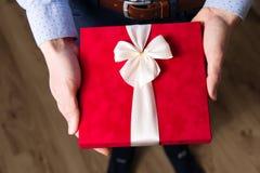 Zamyka w górę mężczyzny mienia walentynki dnia prezenta w rękach, czerwony faborek, prezent etykietka, romantyczna niespodzianka obrazy stock