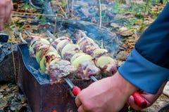 Zamyka w górę męskiego ręka dotyków grilla na skewers Fotografia Stock