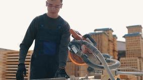 Zamyka w górę młodego cieśli pracownika jest ubranym budowa gogle i munduruje używać drewnianą tnącą maszynę mężczyzn cięcia zbiory
