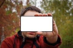 Zamyka w górę młodego człowieka pokazuje pustego ekranu telefon komórkowego nad żółtej zieleni tłem biały pusty ekran dla projekt fotografia stock