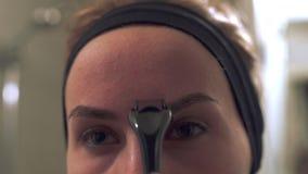 Zamyka w górę młodej kobiety używa derma rolownika dla mikro needling terapii twarz zbiory