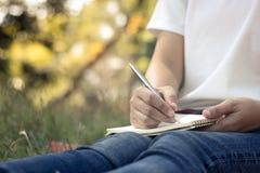 zamyka w górę młodych kobiet pisze na notatniku w parku, pojęcie w edu obraz royalty free
