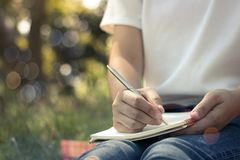 Zamyka w górę młodych kobiet pisze na notatniku w parku, pojęcie w edukaci obrazy stock