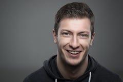 Zamyka w górę markotnego portreta młody nieogolony mężczyzna uśmiechnięty i patrzeje kamerę Obrazy Royalty Free