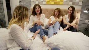 Zamyka w górę materiału filmowego cztery dziewczyny siedzi na gawędzić i łóżku przyjaźń Piękny nowożytny izbowy projekt modny zdjęcie wideo